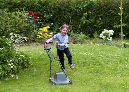 Little boy running with a lawn mower