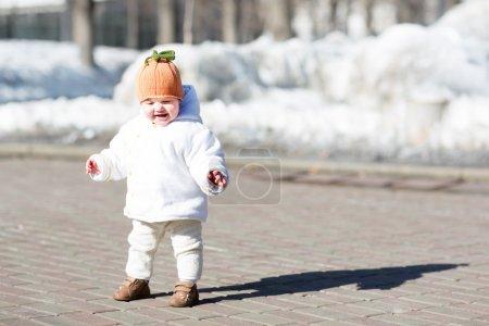 Photo pour Petit bébé faisant ses premiers pas un jour de printemps ensoleillé - image libre de droit