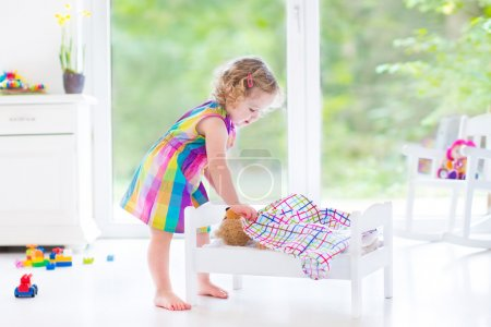 Photo for Happy beautiful curly toddler girl in a pink dress playing with her teddy bear putting him in a toy bed to sleep in a sunny room with big garden view windows and white furniture - Royalty Free Image
