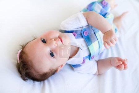 Baby girl in purple overalls