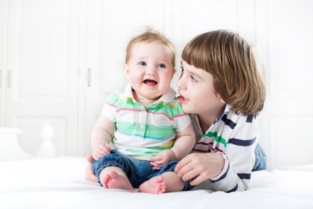 Boy talking to his baby sister