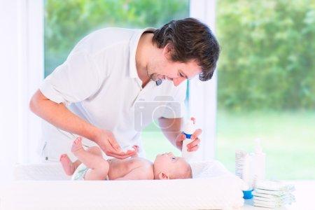Photo pour Jeune père aimant, changer les couches de son fils nouveau-né, tenant la bouteille de lotion dans la main, debout dans une chambre ensoleillée avec une fenêtre vue sur le grand jardin - image libre de droit