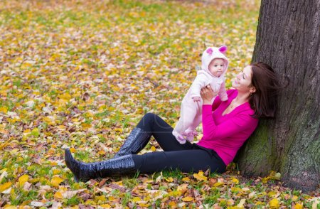 Mother holding her baby daughter under a tree