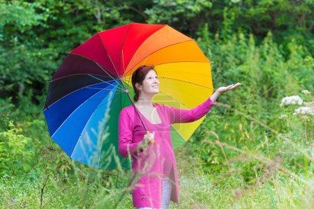 Pregnant woman walking under a colorful umbrella