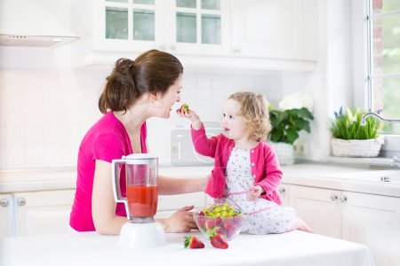 Photo for Happy laughing toddler girl and her beautiful young mother making fresh strawberry and other fruit juice for breakfast together in a sunny white kitchen with a window - Royalty Free Image