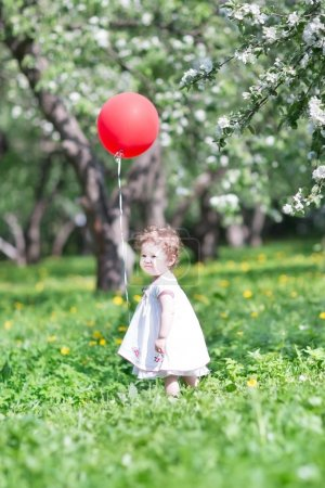 Beautiful little girl playing with flowers
