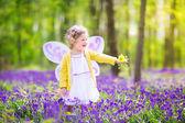Toddler girl in fairy costume in bluebell forest