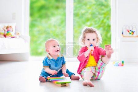 Photo pour Deux petits enfants - une mignonne petite fille et un drôle de petit garçon, un frère et une sœur qui jouent de la musique, qui s'amusent avec un xylophone coloré et une flûte à une fenêtre, des enfants qui suivent des cours de développement précoce - image libre de droit