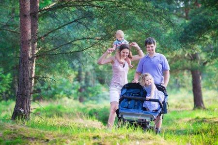 Photo pour Famille active, les jeunes parents et leurs deux petits enfants, fille adorable bambin et un garçon mignon bébé drôle, randonnée ensemble dans une forêt de pins poussant une poussette de jumeau tous terrain - image libre de droit