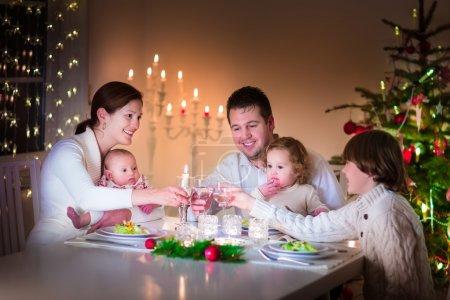 Foto de Gran familia joven y feliz con tres niños disfrutando de la celebración de la cena de Navidad, padres e hijos - niño adolescente, niña y bebé en un comedor oscuro con velas y árbol de Navidad - Imagen libre de derechos