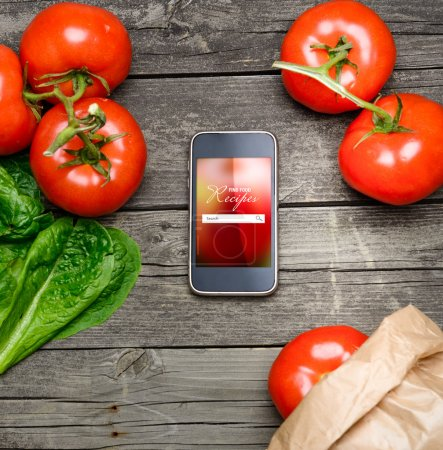 Photo for Online Cooking recipes on smart phone with vegetables on backround. - Royalty Free Image