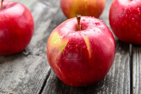 Photo for Fresh apples on old grey wood table with water droplets - Royalty Free Image