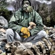 Man in a gas mask sitting on the garbage and holdi...