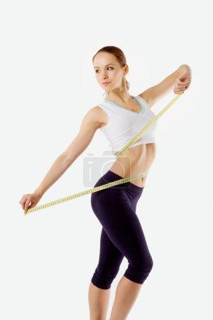 a girl measuring waist