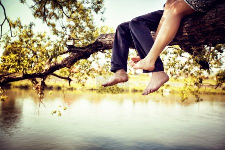 Photo for Young couple in love sitting cross-legged on a tree branch above the river in nice sunny day. Photo is colorized in warm tints. - Royalty Free Image