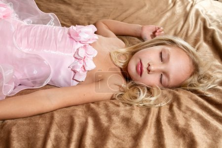 Photo for Beautiful little girl sleeping on bed. Girl is wearing pink dress - Royalty Free Image