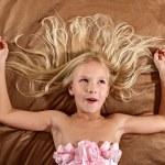 Surprised little girl lying on bed. Girl is wearin...