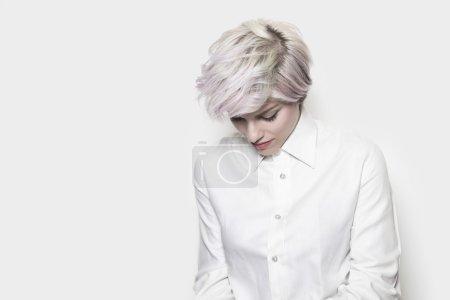 Photo pour Belle fille réfléchie avec les cheveux teints portant une chemise blanche - image libre de droit