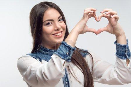 Photo pour Belle jeune femme faire forme de coeur par ses doigts sur le niveau de la tête isolé sur fond gris - image libre de droit