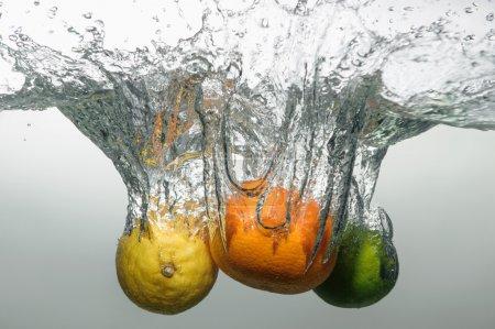 Foto de Tentador maduro naranja, limón y Lima cayendo en el agua con chapoteo grande y burbujas - Imagen libre de derechos