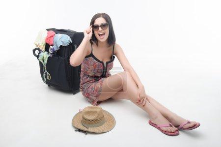 Photo pour Belle fille brune portant des lunettes de soleil et belle robe de soleil assis près de sa valise et riant parce que bientôt elle sera à la mer. Isolé sur fond blanc - image libre de droit