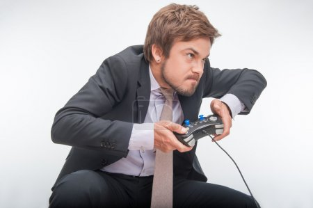 Photo for Very excited handsome businessman in perfect black suit making great efforts to win a video game - Royalty Free Image