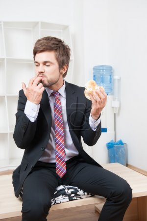 Photo for Handsome young businessman wearing great black suit and colorful tie having a snack during his lunch time in the office - Royalty Free Image