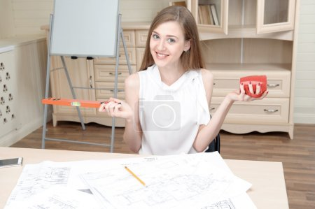 Photo pour Jeune architecte aux cheveux blonds souriant portant un grand chemisier blanc assis à la table avec une jolie tasse rouge satisfaite de sa nouvelle échelle d'orange - image libre de droit