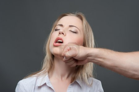 Photo for Poor young fair-haired woman suffering from the cuff of man. Isolated on grey background - Royalty Free Image