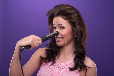Photo pour Portrait à mi-longueur d'une drôle de jeune femme aux cheveux bouclés portant une jolie robe rose se verrouillant le nez avec les fers à friser. Isolé sur fond bleu - image libre de droit