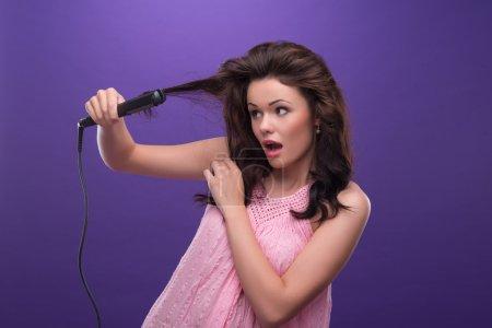 Photo pour Portrait à mi-longueur d'une jeune femme étonnée aux cheveux bouclés portant une jolie robe rose redressant ses cheveux avec les fers à friser. Isolé sur fond bleu - image libre de droit