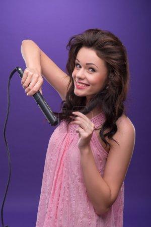 Photo pour Portrait à mi-longueur d'une heureuse jeune femme souriante aux cheveux bouclés portant une jolie robe rose redressant ses cheveux avec les fers à friser. Isolé sur fond bleu - image libre de droit