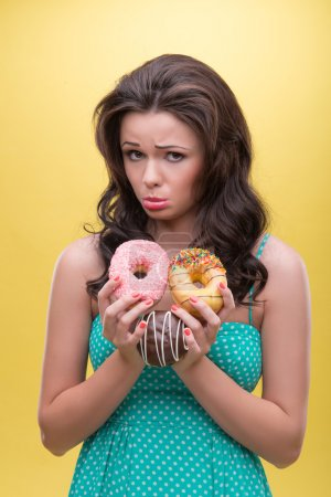 Photo for Half-length portrait of wonderful dark-haired woman wearing nice mint dotted dress showing us that she do not want to share her doughnuts. Isolated on yellow background - Royalty Free Image