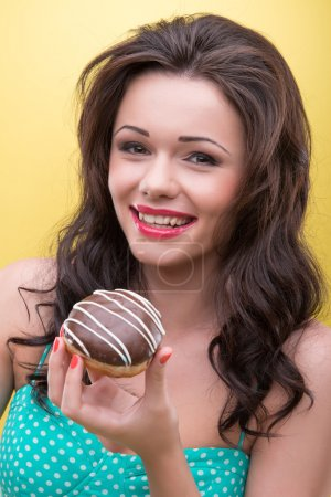 Photo for Half-length portrait of very beautiful smiling dark-haired woman wearing nice mint dotted dress wanted to try her appetizing round doughnut covered with the chocolate icing. Isolated on yellow background - Royalty Free Image