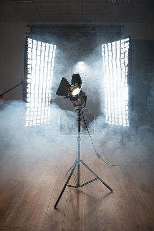 Photo pour Projecteur de cinéma vintage sur chevalet debout sur le sol en bois entre deux énormes projecteurs enveloppés de fumée - image libre de droit