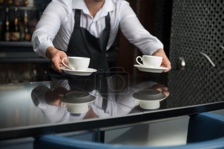 Photo for Barista wearing white shirt and black apron standing at the bar counter suggested us to taste his coffee - Royalty Free Image