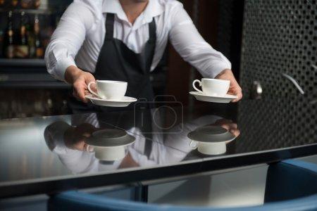 Photo pour Barista portant chemise blanche et tablier noir se tenant à la barre de compteur, nous proposent de déguster son café - image libre de droit