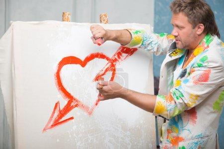 Photo pour Portrait mi-long d'un peintre aux cheveux blonds vêtu d'une veste fraîche peinte à l'écart représentant un beau cœur rouge avec une flèche sur le lin blanc - image libre de droit