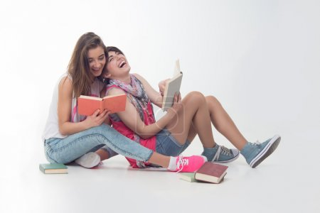 Two attractive teen girls are reading