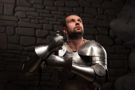 Medieval knight kneeling with sword