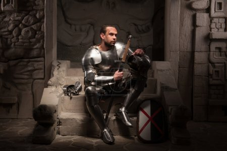 Medieval knight sitting on the steps of ancient temple