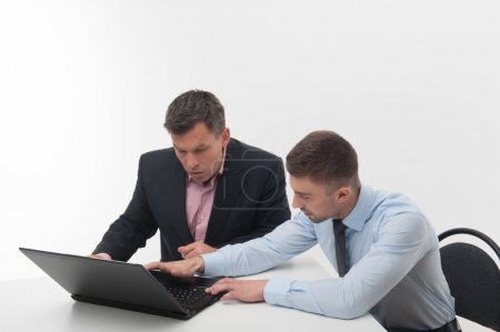 Employee showing something on laptop to his boss