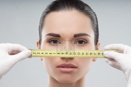 Photo pour Visage de femme mesuré par des mains d'esthéticienne, se préparant pour la chirurgie plastique, isolé sur gris - image libre de droit