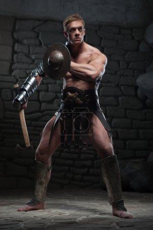 Photo pour Portrait complet de jeune gladiateur guerrier attrayant avec corps musclé tenant bouclier et hache, posant sur fond sombre. Concept de puissance masculine, force - image libre de droit