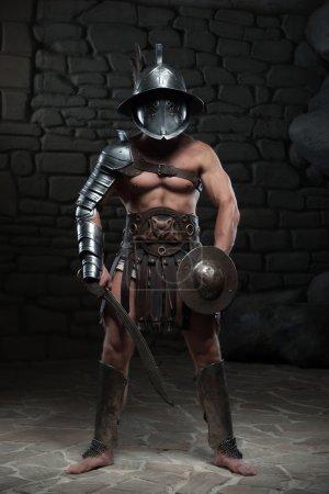 Photo pour Portrait complet de gladiateur guerrier avec corps musclé dans un casque tenant l'épée sur fond sombre. Concept de puissance masculine, force - image libre de droit