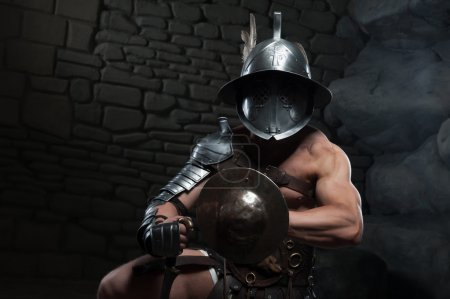 Photo pour Portrait de demi-longueur de gladiateur de guerrier avec un corps musclé en casque, tenant l'épée sur fond sombre. concept du pouvoir masculin, force - image libre de droit