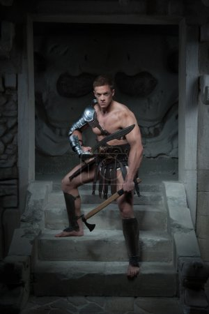 Gladiator in armour standing on steps of ancient temple with swo