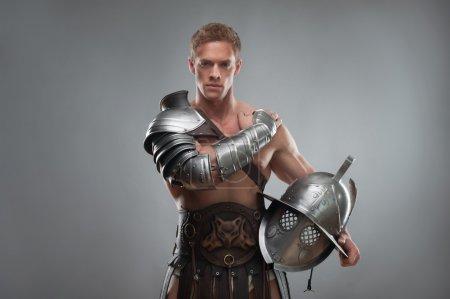 Photo pour Portrait de demi-longueur de gladiator jeune bel homme musclé en armure posant avec casque isolé sur fond gris - image libre de droit