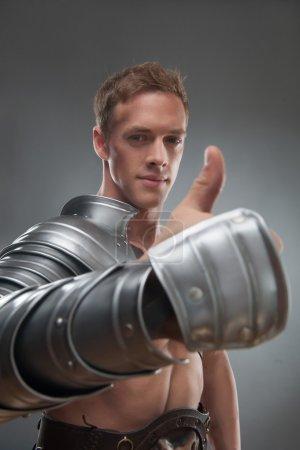 Photo pour Portrait à mi-longueur d'un jeune homme musclé et souriant gladiateur en armure montrant un panneau ok avec les pouces levés, mise au point sélective, isolé sur fond gris - image libre de droit