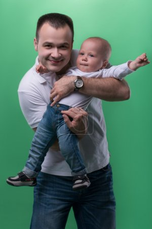 Photo for Half-length portrait of happy smiling handsome father embracing his son baby boy, baby is stretching his arms, family concept, isolated on green background - Royalty Free Image